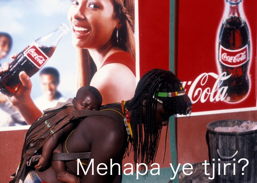 ©Corina Gertz - Young Himba mother in front of a giant Coca Cola ad in Opowo, Namibia (translation of the question: What do you really need?), 3 x 2,16 m, 2011